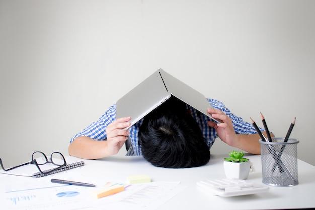 ビジネスマンは、大変な作業で頭が痛くなり、ラップトップを使って頭を覆います。