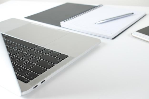 ノートパソコン、スマートフォン、白いテーブルの上のノートと仕事場