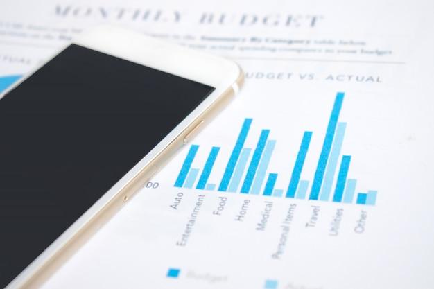 ビジネスマンの財務グラフ上のスマートフォンと近代的なオフィスデスクイメージ