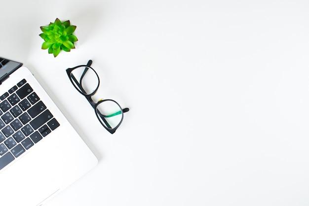 ノートパソコン、メガネ、白い背景の上のコピースペースを持つ小さな木の近代的な職場。上面図。