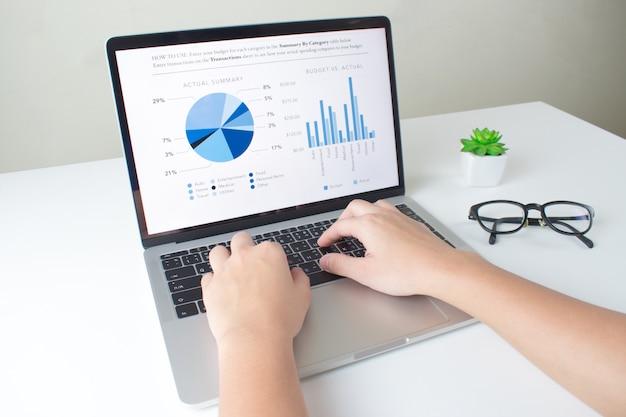 Взгляд со стороны, современный стол офиса портативного компьютера с финансовым дисплеем диаграммы.