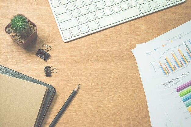 Закройте вверх, коричневый деревянный стол с взгляд сверху компьютера, карандашей, бумаги, зажимов и кактуса.