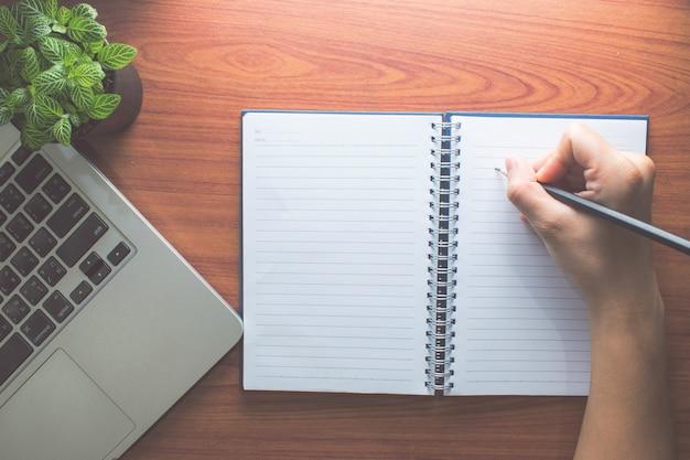 アジア、人間の手が鉛筆で開かれた本を書いています。コンピューターと鉢植えの植物の近くです。