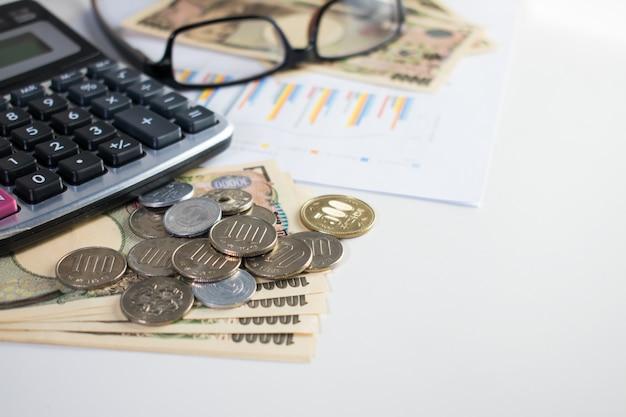 Сбережения, расчет японская валюта, банк иены и монеты с калькулятором, ручками, очками и бумагой. азия