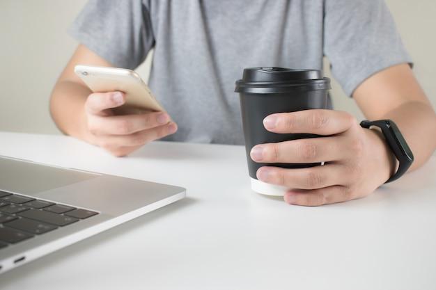 Руки серой футболки используют смартфон на столе и пьют чашку кофе.