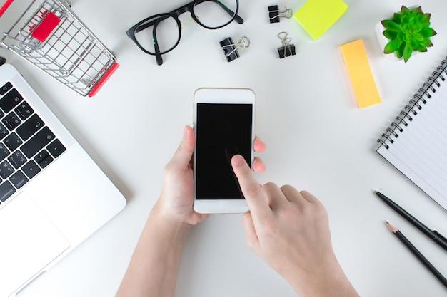 オンラインショッピングに携帯電話を使用している女性の平面図。コンセプトテクノロジー。
