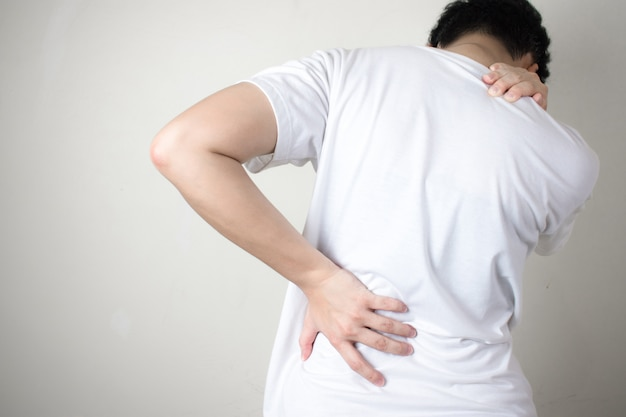 背中の痛み。背中の痛み、白い背景で隔離の女性。