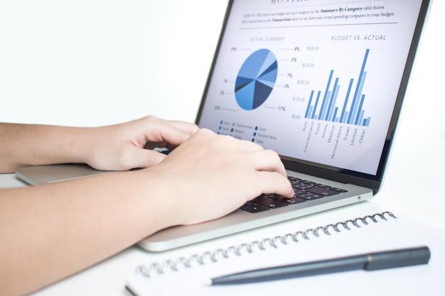 ビジネスマンはラップトップを使用して統計を分析します。