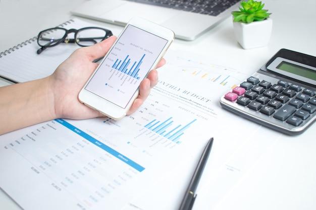 ビジネスマンはスマートフォンを使用して、白いテーブルの財務グラフを計算します。