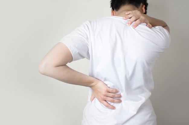 アジア人の背中には肩の痛みがあります。手で肩と背骨をつかみます。