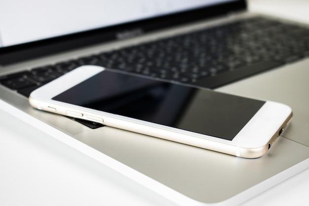 ノートパソコンの机の上のクローズアップスマートフォン。