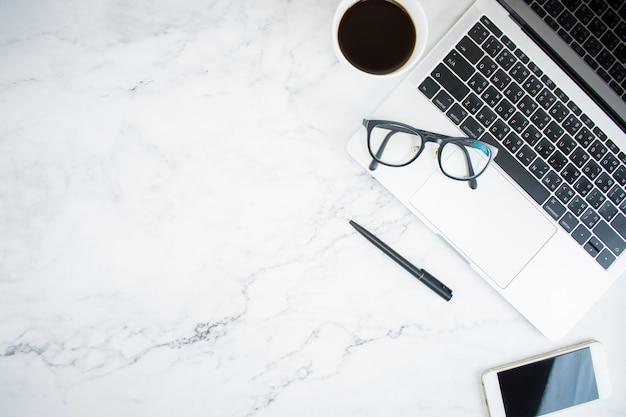 ラップトップ、スマートフォン、メガネ、コピースペース、フラットレイアウトのトップビューでコーヒーと大理石のテーブル。