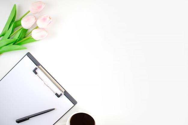 チューリップ、クリップボード、ペン、白い背景の上のコーヒーと白いテーブルのトップビュー画像。