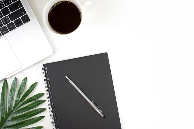 白い色でフラット横たわっていた、トップビューオフィス現代作業テーブル。アクセサリーはラップトップ、ノートブック、ペン、コーヒー、コピースペース付きの緑の葉で白い色で動作します