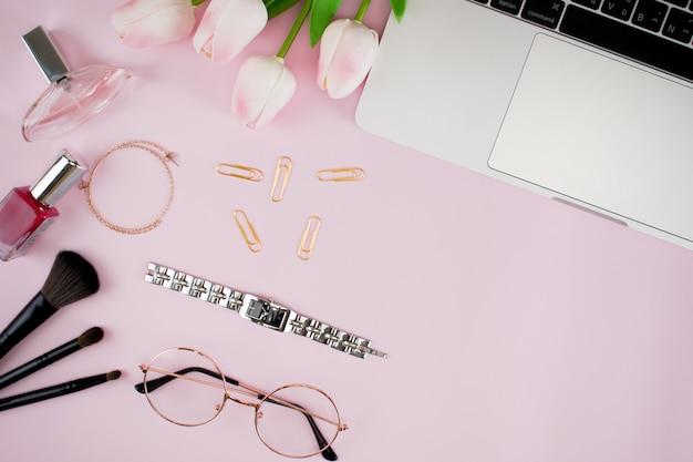 ピンクのパステルピンクの紙の上に平らに横たわっているファッションアクセサリー。
