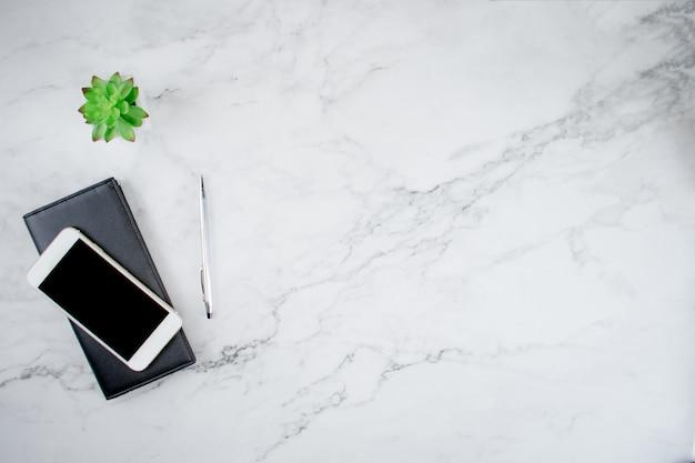 レザーバッグのスマートフォンの平面図とコピースペース、フラットレイアウトと近代的なオフィスデスクの植木鉢。