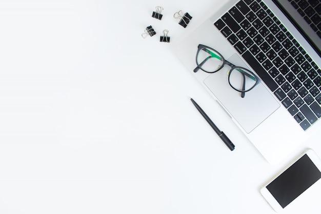 ノートパソコン、眼鏡、白いテーブルの上のスマートフォンとワークスペース