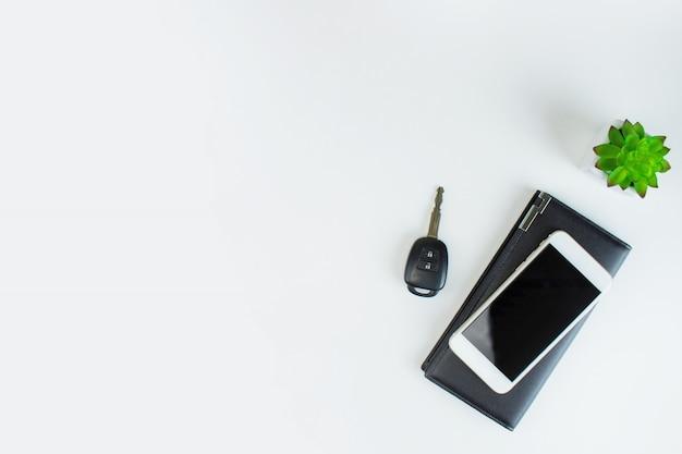 白い背景の上の車のキーと植木鉢と黒革のバッグに置かれたスマートフォンの画像
