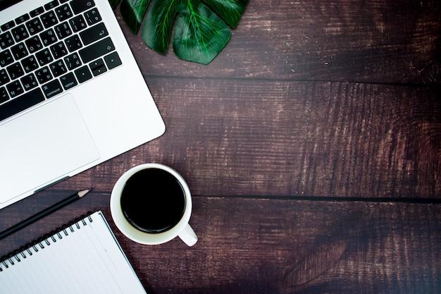 ラップトップコンピューター、コーヒー、ペン、コピースペースと葉のトップビューオフィステーブル木製デスク。