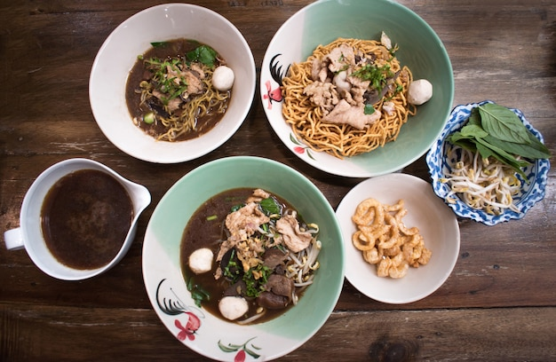 木製テーブルビンテージスタイル、アジア料理に新鮮な野菜とミートボールのアジアンヌードルスープ。上面図