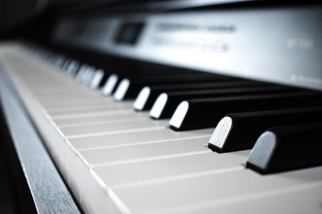 音楽室の黒いピアノのキーのクローズアップ。