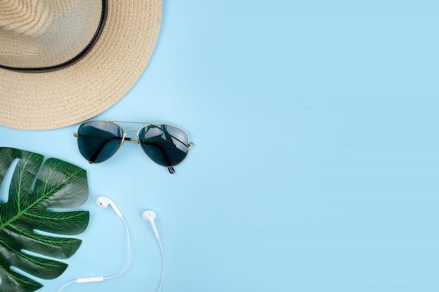 Каникулы путешественника с шляпой и солнцезащитными очками на синем фоне