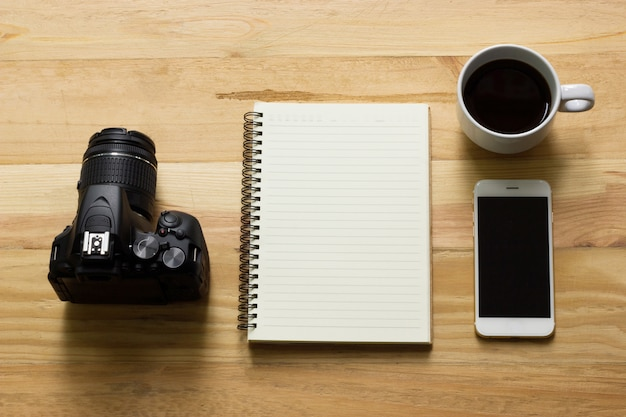 写真家の平面図、カメラ、ノートブック、コーヒー、スマートフォンを備えた木製のテーブル。