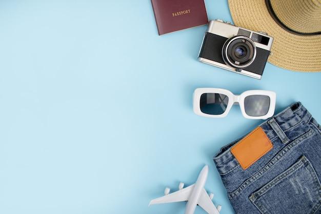 トップビュー、ジーンズ、フィルムカメラ、パスポート、帽子と青色の背景を持つ観光アクセサリー。コピースペース付き。