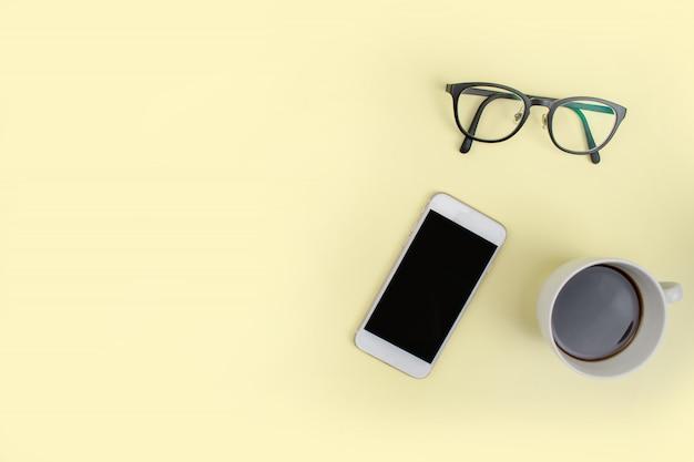 色付きの背景にスマートフォン、コーヒー、メガネのコピースペースを持つ画像の最小限のスタイル