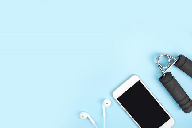 上面図。青のダンベル、スマートフォン、ヘッドフォンとスポーツアクセサリー。コピースペース付き。