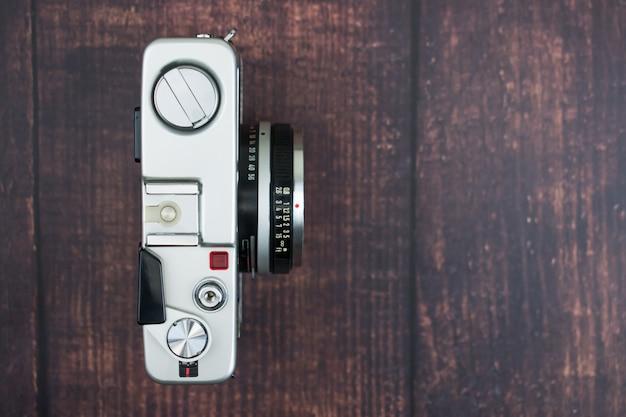 古い木製の背景にビンテージカメラのフラットレイアウト。孤立した背景。上面図。