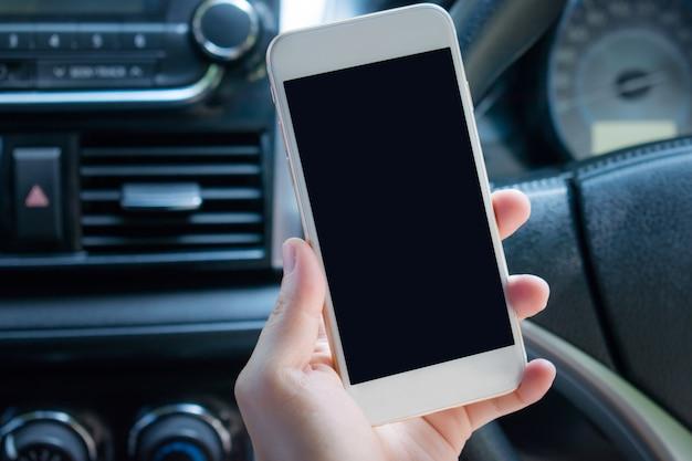 車の中でスマートフォンを使用して手のクローズアップ。