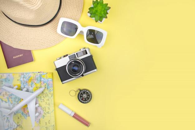 黄色の背景に帽子、地図、スマートフォン、フィルムカメラ、サングラスをかけた少女の休暇。上面図。