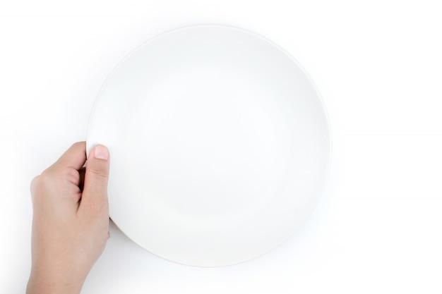 Крупный план, одной рукой держит белую тарелку, вид сверху