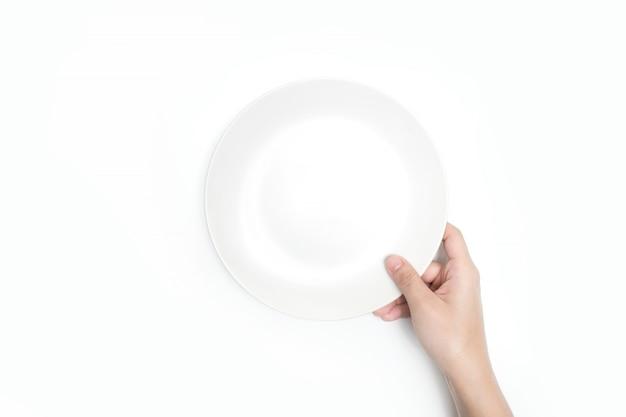 Крупный план, держит белую тарелку, вид сверху