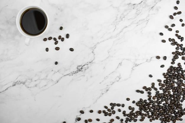 大理石の背景にコーヒーと茶色のコーヒー豆の平面図。