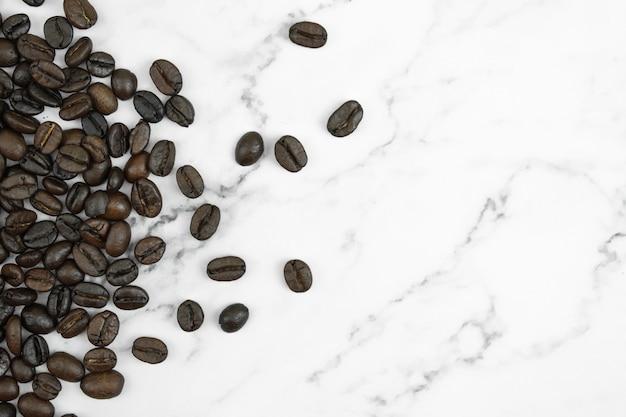 コピースペースを持つ大理石の背景に茶色のコーヒー豆。上面図。