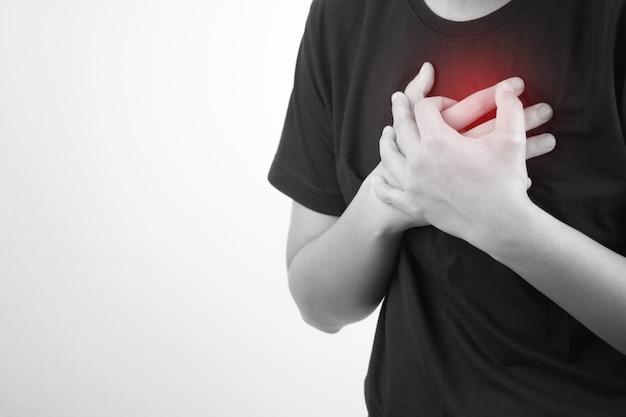アジア人は白に心臓発作を起こしています。孤立した背景。健康と医療