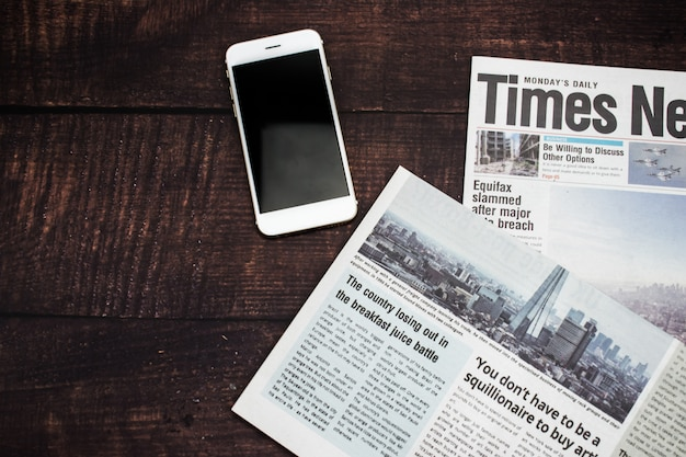 新聞とトップビューの木製テーブルの上のスマートフォン。