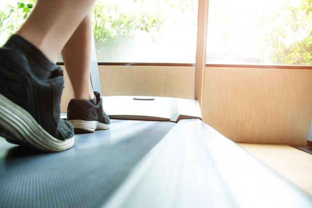Человек работает в тренажерном зале на беговой дорожке, чтобы тренироваться