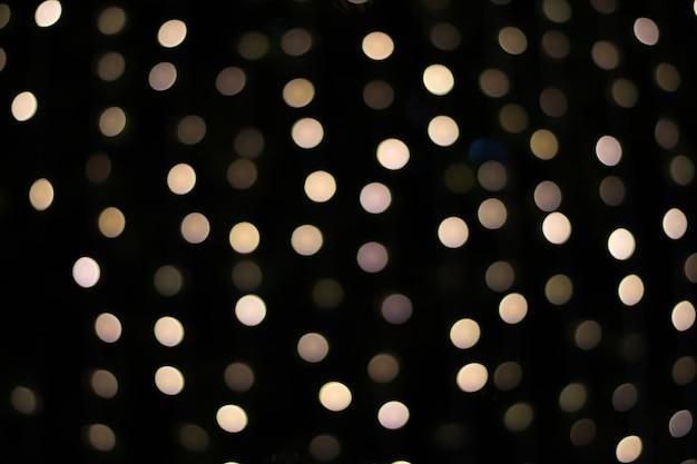 黒の背景、ぼやけたライトに黄金のボケ