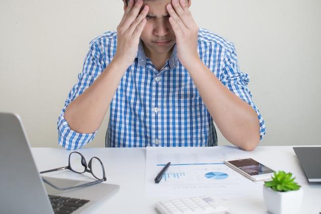Портрет азиатского человека в клетчатой рубашке, имеющие сильные головные боли во время работы в офисе.