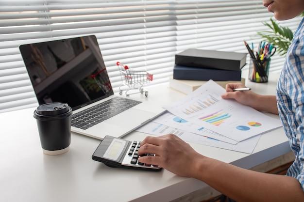 会計ビジネスマンは、経済コスト、会計概念を計算する青い格子縞のシャツを着ます