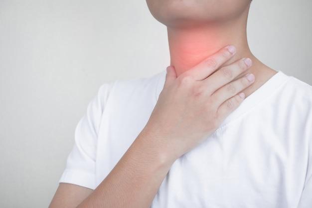 Азиатские люди чувствуют боль в горле из-за тонзиллита, используя свои руки, чтобы коснуться шеи.