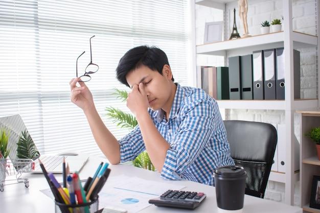アジアの人々は疲れており、オフィスで働いている間に手を使って顔を覆っています
