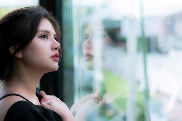 魅力的な女性は常に外を見て、待っているボーイフレンド