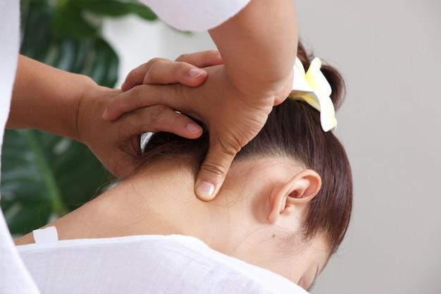 女性はタイ風の首のマッサージをしています