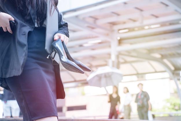 女性は黒いハイヒールの靴を運んでいます。彼女は苦しんでいます。