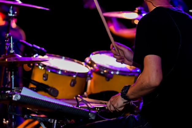 Музыканты играют на ударных на сцене.