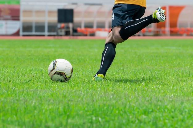 Крупным планом, футболисты собираются ударить мяч, который находится на газоне.